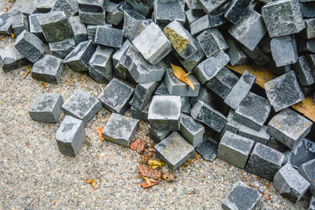 Pile of black natural stone cubes for making outdoor pavement tiles. Chaotic stack of broken road tiles. Construction background of mess geometric backdrop with grey shades pavement stone blocks Stockfoto