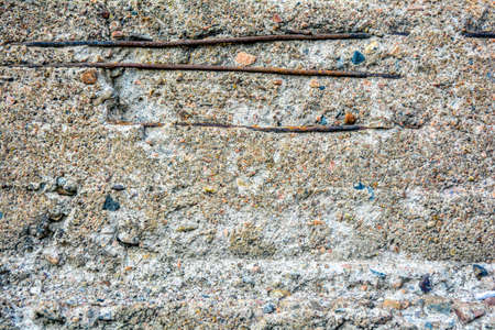 Texture of crumbling concrete wall with horizontal bars of rusty iron armature. Through damage in old rough concrete surface with small stones, details of internal reinforcement are visible