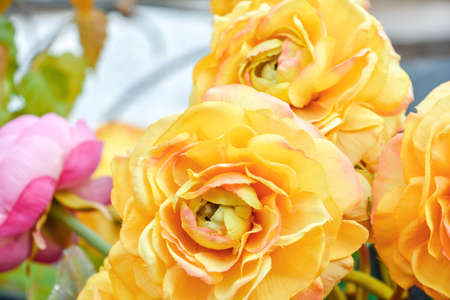 Close up of artificial yellow and pink rose flower bouquet. Silk flowers bunch