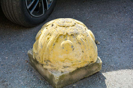 Element of sidewalk design and protection from car parking and detail of car wheel. Yellow embossed hemisphere limiter of parking for cars on city street