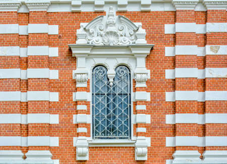Close-up of ancient vintage arch window with cast iron white painted deorative lattice and white antique plaster patterns 스톡 콘텐츠