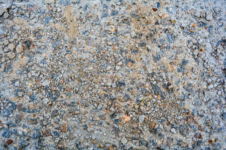 Ground street surface of broken asphalt or cement with pothole and stone pebbles. Damaged concrete road sidewalk with old dangerous pothole. Urban texture of old stone floor 스톡 콘텐츠