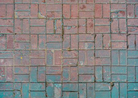 Grunge cracked red street tiles with blue paint. City street pavement cobblestone pattern. Urban civil footpath floor tiles 스톡 콘텐츠