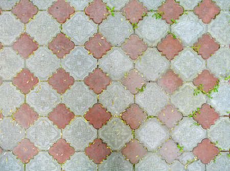 Red and gray road tiles on city street pavement with growing grass in mortar. Road construction background. Cobblestone pathway paved with grey and red decorative bricks. Road cover surface texture