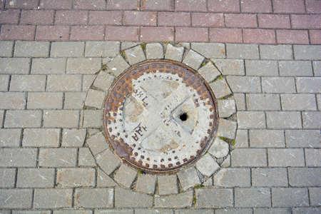Ancient cast iron rusty manhole on pavement sidewalk of city street. Detail of urban street