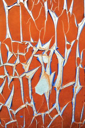 Texture of old bursting pvc paper on concrete wall. Orange cracked protective membrane with twisted edges with blue wrong side. Damaged peeling wall covering, rolled along edges of cracks in rolls