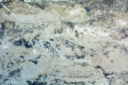 Texture of rough concrete or cement surface with stains of black paint and dirt. Old ruined surface of cityscape
