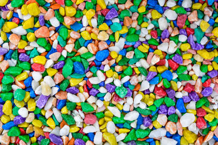 Vibrant colorful marble fine gravel. Simple stone background with bright multicolor pebbles. Stone texture. Top view of ground decor for garden with colorful natural stone