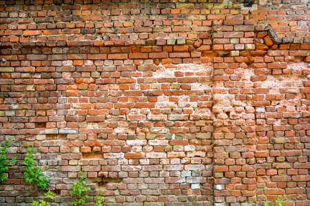 Old ruined orange brick wall with concrete remains and cracks. Damaged antique brick wall texture 스톡 콘텐츠