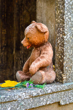 Weathered teddy bear toy with yellow maple leaf and flowers in opening of old crypt with child burial in cemetery in fall. The concept of sadness, grief over loss of child, death