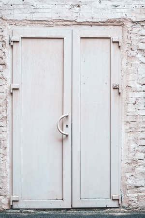 Front exterior doors of old brick building. White bricks wall with white painted old double door