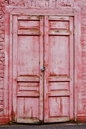 Front exterior doors of old brick building. Red bricks wall with red painted old double door