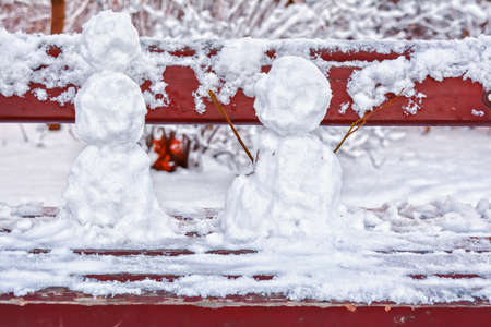 Several crooked and messy figures of snowmen from first winter snow stuck together by child on bench in city square. Undecorated snowman 스톡 콘텐츠