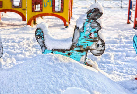 Old children carousel with blue donkey on snow-covered children playground is covered with white fluffy snow. Snowdrift with wooden donkey