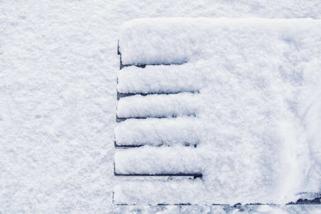 Top view of detail of snow covered wooden bench in winter park. Red simple bench with white fluffy snow on clear white snow background