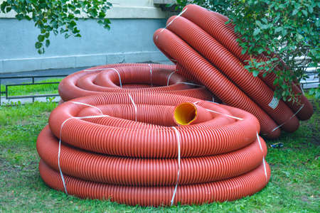 Coils of new red plastic pipe with rain drops on city lawn with green grass. Red plastic tubing for underground cable protection. First floor of skein of red corrugated tube. Plastic pipes background