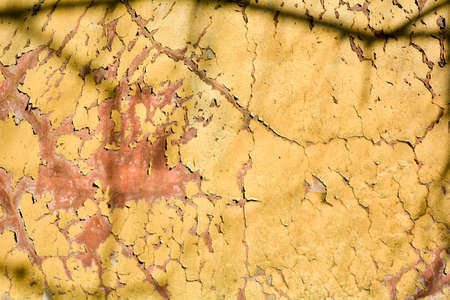 Old grunge messy plaster wall with peels of paint. Rough urban concrete wall texture with damages Zdjęcie Seryjne