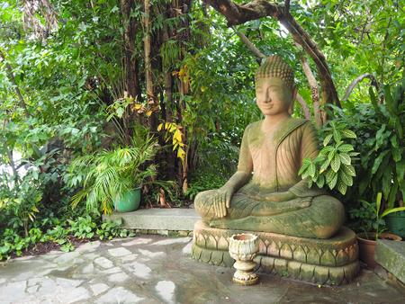 Phnom Penh, Cambodia - 5 May 2017: Buddha statue sitting under the tree in Royal Palace Phnom Penh.
