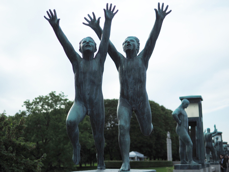 Oslo, Norway - August 27, 2017: Two Boys Running with Arms towards the Sky at Vigeland Park in Oslo, Norway, sculpted in bronze by Gustav Vigeland. Редакционное