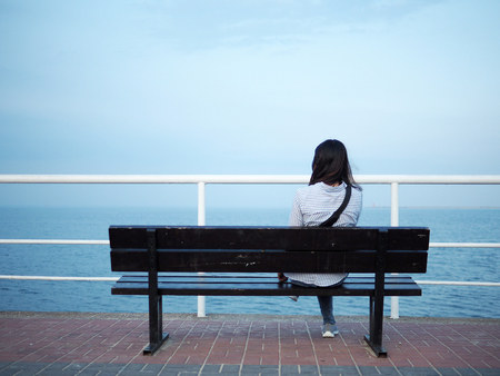 Woman back sitting on bench looking at the sea, girl back. Standard-Bild