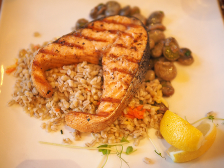 Blurred background of Salmon grill with cereal and lemon, Polish cuisine.