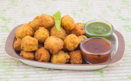 Dal vada, a traditional Indian delicious snack, made from deep frying portions of lentil batter and gram flour, indian and pakistani usually with green fried chilli and onino Stock Photo