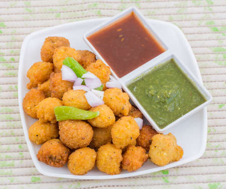 Dal vada, a traditional Indian delicious snack, made from deep frying portions of lentil batter and gram flour, indian and pakistani usually with green fried chilli and onion Stock Photo