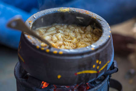 stirred: Vegetarian Vegetable pasta cooking in wooden fire Stock Photo