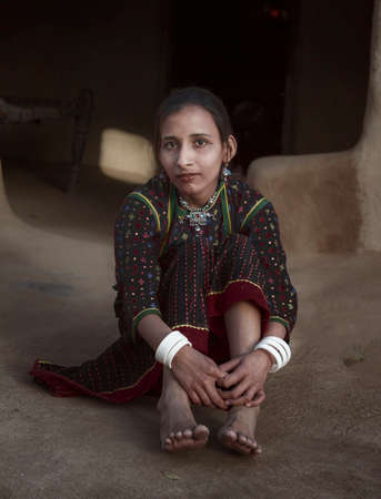 Rural Girl from Asia sitting at her hut