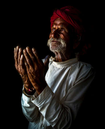 Indian old Man praying to god for every thing good Stock Photo