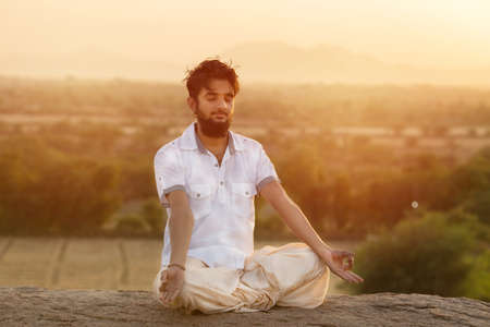 Young Indian man on top of mountain sitting in yoga pose. Stok Fotoğraf