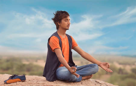 Young Indian man on top of mountain sitting in yoga pose. Standard-Bild - 101551150