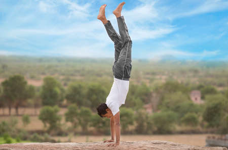 Young Indian man on top of mountain in adho mukha vrksasana  yoga pose.