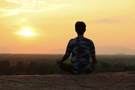 Young Indian man on top of mountain sitting in yoga pose. Standard-Bild - 101550916