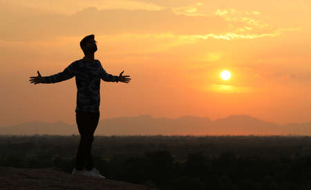 Silhouette boy walking alone in sunset background Stock Photo