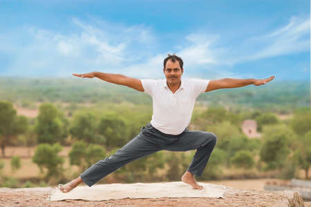 Young Indian man on top of mountain sitting in yoga pose. Standard-Bild - 101550833