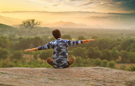 Young Indian man on top of mountain sitting in yoga pose. Standard-Bild - 101550828