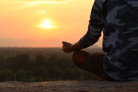 Young Indian man on top of mountain sitting in yoga pose. Standard-Bild - 101550761
