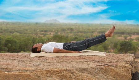 Young Indian man on top of mountain sitting in yoga pose. Standard-Bild - 101550776