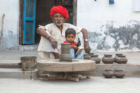 ANDORE, RAJASTHAN INDIA - JULY 20, 2016: Indian potter with his grandson making clay pots on a wheel in the village of andoure, near sirohi,  Rajasthan, northern India. 에디토리얼