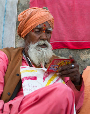 Vastanji, India - January 08, 2014: holy man reading holy book at Muni maharaj Temple in vastanji village, Sadhu devoted his whole life in meditation after wear Saffron religion apparel in india, muni maharaj festival held once in every year, all india ho