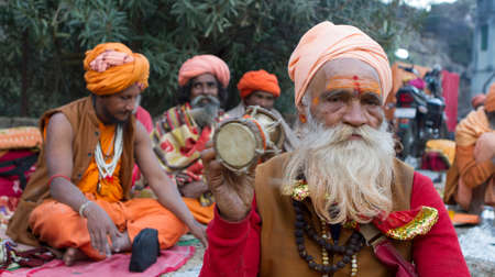 Vastanji, India - January 08, 2014: holy man playing Damaru at Muni maharaj Temple in vastanji village, Sadhu devoted his whole life in meditation after wear Saffron religion apparel in india, muni maharaj festival held once in every year, all india holy