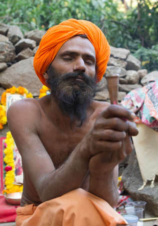 Vastanji, India - January 08, 2014: holy man smoking at Muni maharaj Temple in vastanji village, Sadhu devoted his whole life in meditation after wear Saffron religion apparel in india, muni maharaj festival held once in every year, all india holy man tog