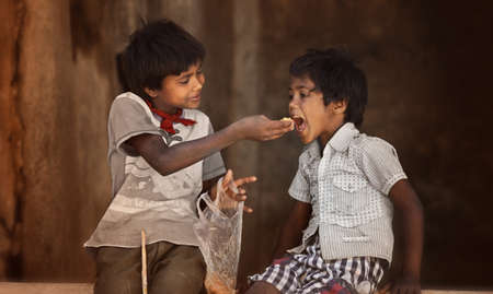 SARNESWAR, INDIA -MARCH 17, 2016: Unidentified poverty Boy gives food to his littel brother, about 32.7% percent of Indians are extremely poor yet, Sarneswar India, March 17, 2016 Editorial