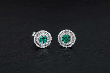 Close up of diamond earrings isolated on black rock background Standard-Bild
