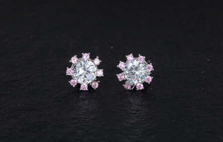 Close up of diamond earrings isolated on black rock background Stock Photo