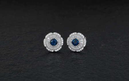 Close up of diamond earrings isolated on black rock background Фото со стока