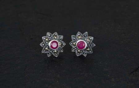 Close up of diamond earrings isolated on black rock background Standard-Bild