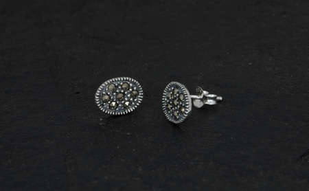 Close up of diamond earrings isolated on black rock background