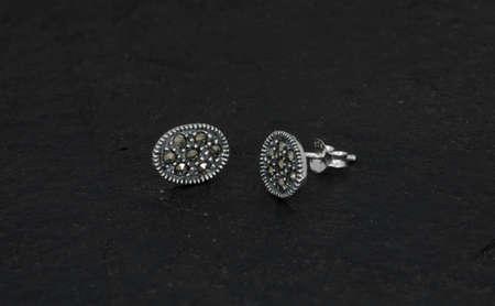 Nahaufnahme von Diamantohrringen auf schwarzem Rockhintergrund isoliert